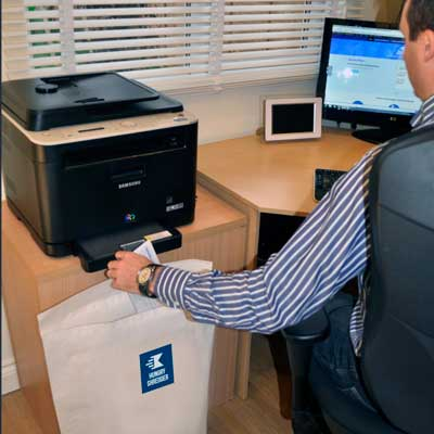 Man at desk using paper shredding service sack from Hungry Shredder